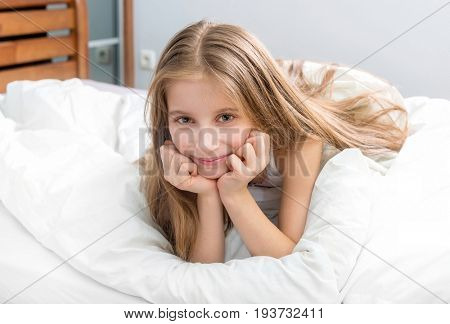 child wrapped with a white blanket, awake