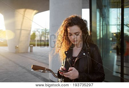 Serious teenage girl taking a rest during bike ride on city streets on weekend and messaging her boyfriend via mobile phone standing outdoors with bicycle. sun shining through her curly hair