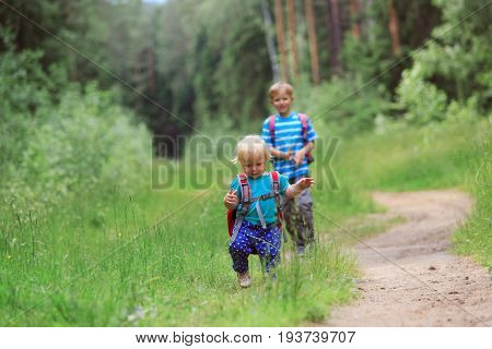 three kids with backpacks go to school, daycare or hiking in nature