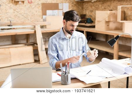 Serious young wood master with beard is sitting at desk and holding special ruler and little timber item in hands. He is making measurement of manufacture and looking at it attentively