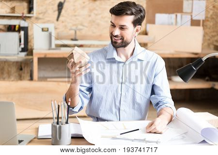 Waist up portrait of happy young lumber craftsman with beard sitting at his workplace and holding little faceted manufacture made of wood. He is looking at it with joyful interest