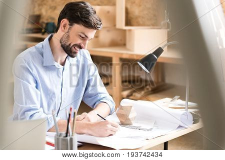 Happy young lumber craftsman is sitting at his table and making drafts of new manufacture. He is drawing sketches on paper by graphite pencil