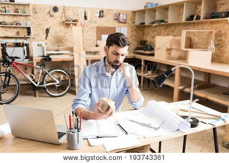 Waist up portrait of serious young woodworker with beard is sitting at table. He is leaning by cheek on one hand and gazing at timber polygon holding it in other hand