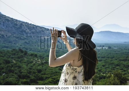 Woman traveler photographing beautiful natural view mountains on the island of Crete. Concept - tourism, travel, photos from vacation.
