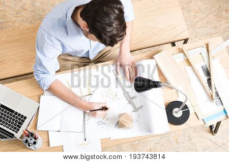 Top view of young woodworker sitting at his working place and drawing sketches of lumber products. He is making pictures by graphite pencil