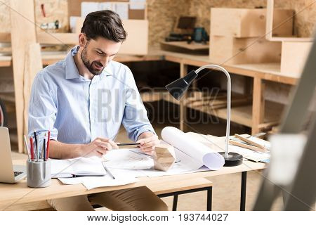 Happy young lumber craftsman with beard is sitting at working desk and looking down at his sketches. He is holding pencil in hands and smiling