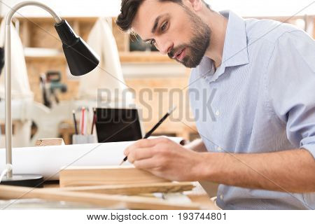 Pensive young craftsman with beard is carefully doing marks on timber strip by graphite pencil at his desk. He is using table lamp for better illumination