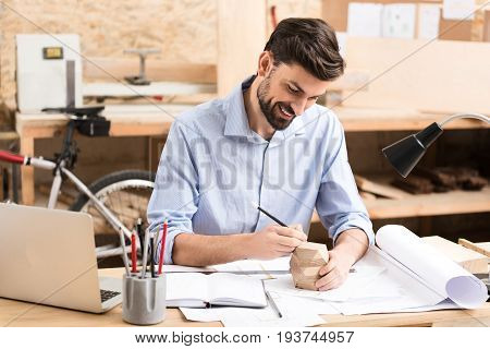 Waist up portrait of joyful young lumber craftsman with beard sitting at his desk and putting marks on wooden polygon by graphite pencil. He is leaning on table with various sketches