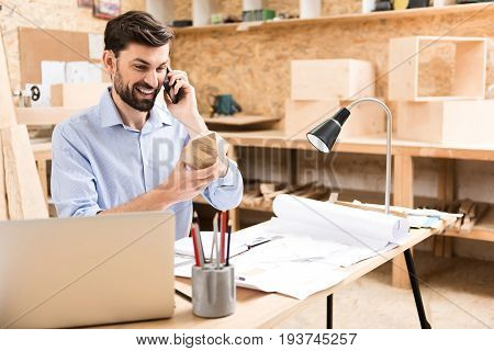 Waist up portrait of happy young bearded lumber craftsman sitting at desk and talking through cell phone. He is looking at timber polygon in hand and smiling broadly. Table lamp illuminating workplace
