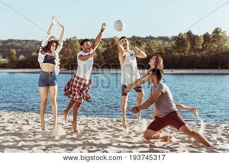 young smiling friends playing beach volleyball on riverside at daytime poster