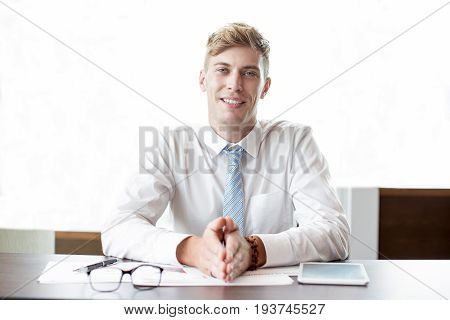 Closeup of smiling adult business man looking at camera, keeping hands together and sitting at office table. Front view.