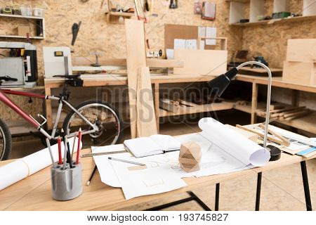Workplace of lumber craftsman with sketches on whatman paper, graphite pencils, lamp and other stationery on table. Carpenter desks with timber planks built in along walls on background