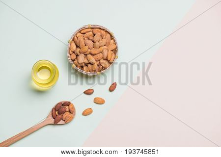 Almonds on light background. Almond nuts in spoon.