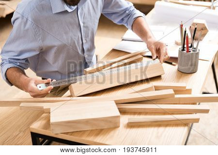 Close up of hands and body of wood master sitting at desk and making measurements of various timber strips and planks by long aluminium ruler. Penholder with graphite pencils standing on table