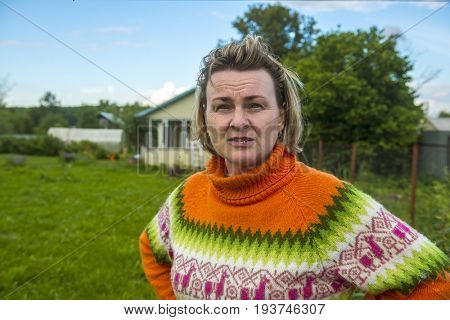Adult woman in a sweater in the garden