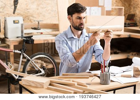 Waist up portrait of pensive young bearded woodworker sitting at table with planks, paper sketches and graphite pencils. He is holding plank by both hands at eye level and gazing at it