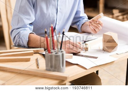 Close up of hands of woodworker sitting at table and drawing sketches on sheet of paper by graphite pencil. Timber sticks and polygon, penholder with pencils, ruler lying on desktop