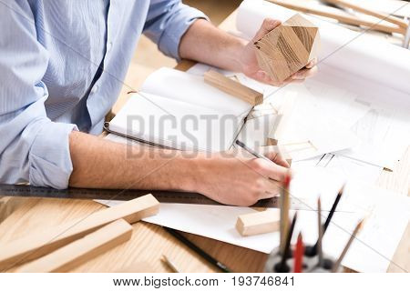 Close up of hands on wood master sitting at desk and drawing sketches by graphite pencil. He is holding timber polygon in one hand. Notepad, lots of sticks and whatman paper lying on table