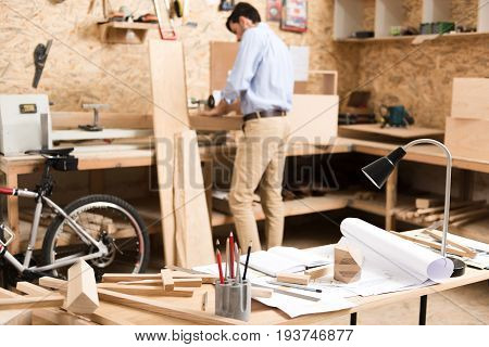 Woodworking workshop with worktable of carpenter with different wooden planks, pencils and drawings. Wood cutting stand, bike, various professional tools and young man are on background