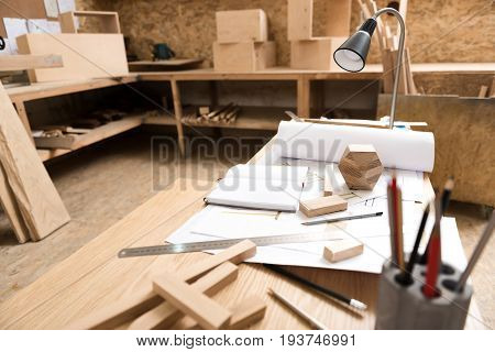 Workplace. Focus on wooden table with reading lamp with pencils and planks on it. Rolls of drawings are opening on board. Shelves with professional tools on background