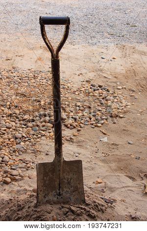 Old rusty shovel stab above the sand.