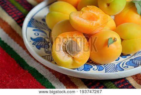 Ripe apricots fruits on rustic plate, close up
