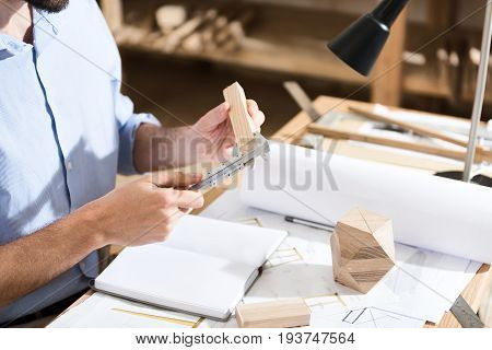 Precision throughout. Close up of hands of young male carpenter is holding calipers and measuring value of wooden plank. He is sitting at desk in his workshop