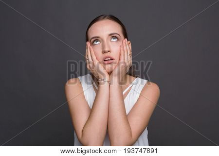 Bored girl rolling her eyes and touch cheeks. Tired young woman demonstrates her fatigue, monotony concept