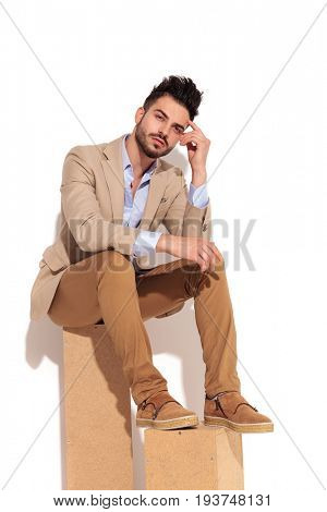 thoughtful young business man sitting on wooden boxes on white background