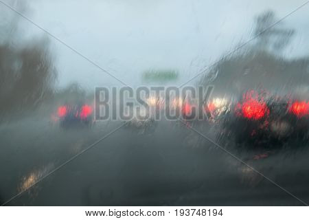 Driving with heavy rain on car windscreen on State Highway 1 Auckland New Zealand NZ - car in front does not have lights on