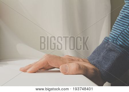 Man Leaning And Puts His Hands Down On White Cloth Background