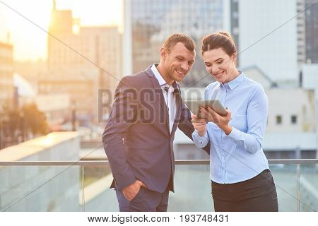 Smiling business couple with tablet. Cheerful man and woman, city.