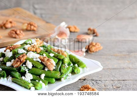 Warm green spring bean salad recipe. Home green spring bean salad with cottage cheese, raw pelled walnuts, garlic and spices on a plate and an old wooden table. Rustic style