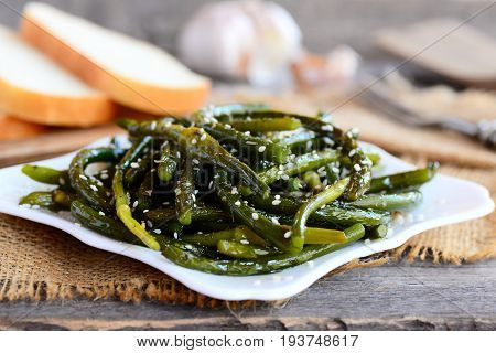 Crunchy garlic stalks. Fried young garlic stalks with spices and sesame seeds on a white plate. Rustic style. Healthy and cheap vegetarian food. Closeup