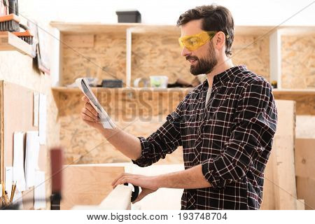 Checking sketch. Positive young woodworker is standing near professional lathe and looking at his notepad with smile. He is laboring in safety glasses
