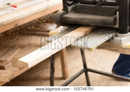 Professional equipment. Close-up of planer and thickness planer with wooden plank on joinery during operation