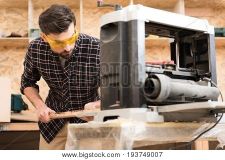 Accurate work. Serious young carpenter wearing safety glasses is holding wooden bar and working on thickness planer with concentration. Focus on man