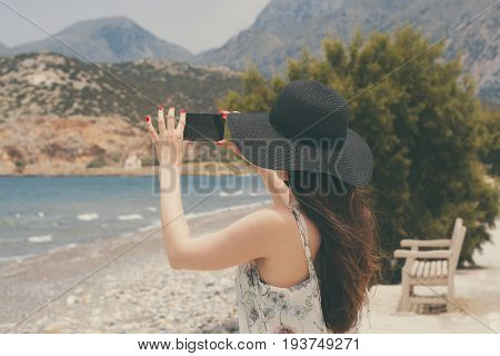 Female traveler photographing on smartphone beautiful natural views of the sea and the mountains on the island of Crete. The concept of tourism, travel, vacation photos