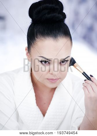 Portrait Of A Brunette Woman Putting On Make Up In Front Of The Mirror