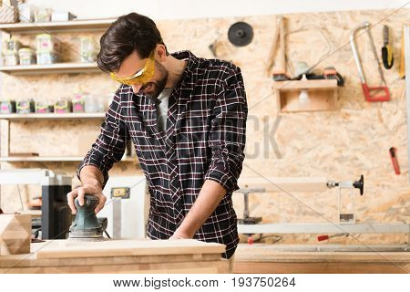 Good mood. Joyful bearded craftsman with hand-held sander and protective glasses is polishing wooden plank while standing in his workshop. Copy space in the right side