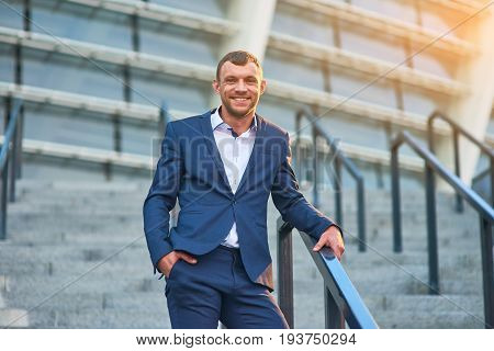 Smiling businessman outdoor. Happy guy in a suit. What is social status.