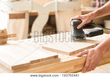 Real professional. Close-up of hands of woodworker with hand-held sander. He is polishing wooden plank in workshop carefully. Copy space in the left side