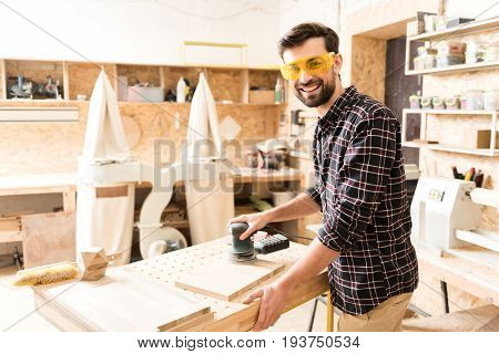 Enjoy what you do. Portrait of cheerful pleasant bearded woodworker wearing protective glasses is standing with hand-held sander and looking at camera with joy. Copy space in the left side