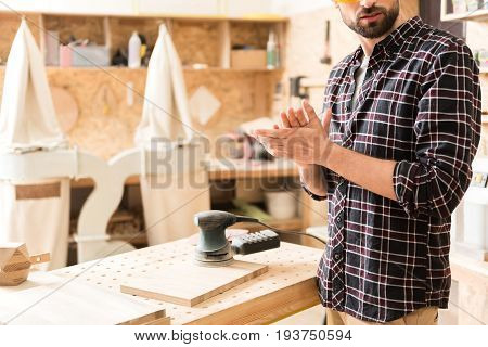 Finished work. Bearded young joiner is standing near his workplace and rubbing his hands. Hand-held sander is on wooden plank. Copy space in the left side