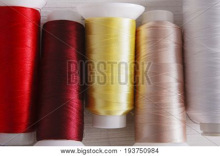 Colorful thread spools on wooden table close up. Sewing string. Art, handicraft concept