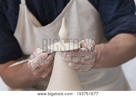 Hands of a potter in the period of work on the production of clay products