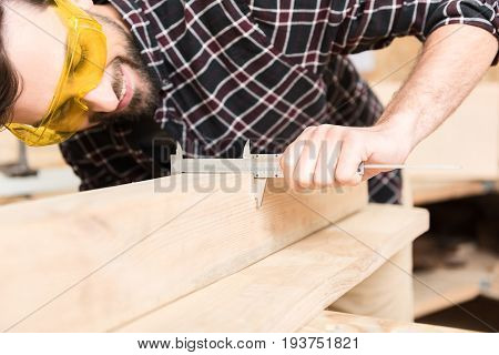 Enjoying process. Close-up of calipers in hand of positive young woodworker wearing protective glasses is measuring width of wooden plank with concentration
