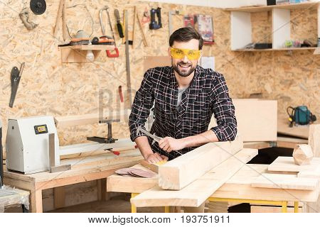 Good mood. Portrait of cheerful experienced carpenter wearing protective glasses and leaning on table with wooden bar. He is holding calipers and looking at camera with smile