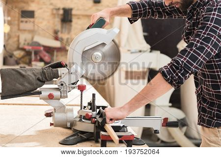 Busy worker. Highly skilled active bearded craftsman is using radial arm saw while laboring in his workshop