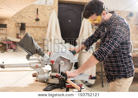 Feeling confident. Experienced carpenter wearing safety glasses is working in his workshop while using radial arm saw to cut wooden plank. Copy space in the left side